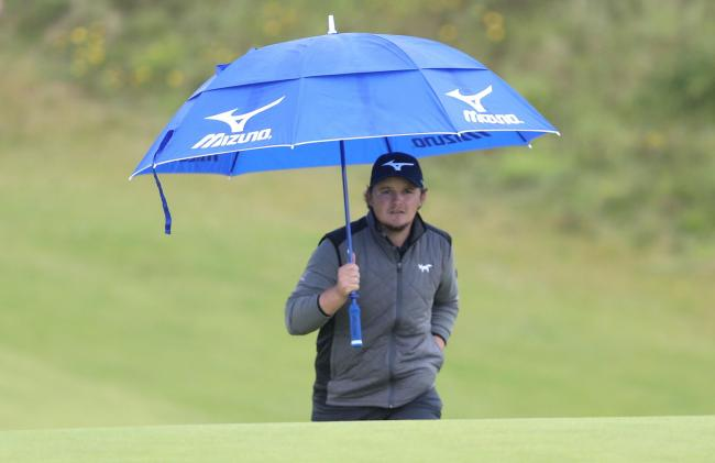 Eddie Pepperell takes shelter from the rain on his approach to the sixth green during a tough second day of the Open Championship at Royal Portrush yesterday 		           Picture: David Davies/PA Wire