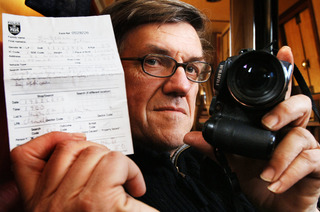 Stephen Russell with his camera and the paperwork he was given by the police