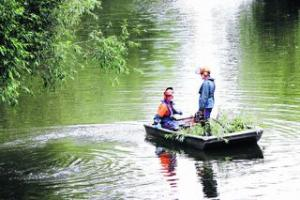 Environment Agency workers on the River Cherwell clear obstructions as part of anti-flood work