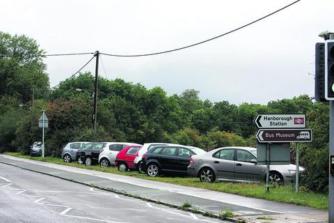Cars parked on a verge alongside the A4095 at the entrance to Hanborough station