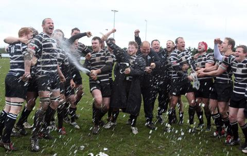 Chinnor players and coaches enjoy a champagne moment after defeating Tonbridge Juddians at Kingsey Road