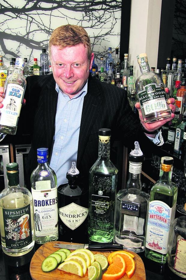 Jeremy du Plessis with some of the 163 different gins The Feathers Hotel bar boasts. Picture: OX52187 Ric Mellis