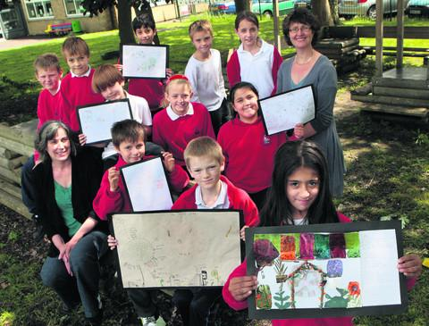 St Nicholas Primary School in Old Marston is looking to create a sensory garden. Johanna McNulty, left, and Carol Kelsey, right, with children holding up the plans. Aisha Aziz is pictured at the front. Picture: OX52564 Antony Moore