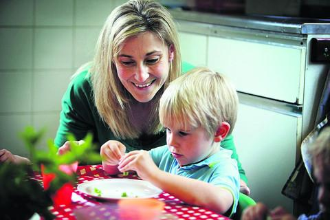 Headteacher Ruth Salway pods peas with three-year-old Oliver Pitts –