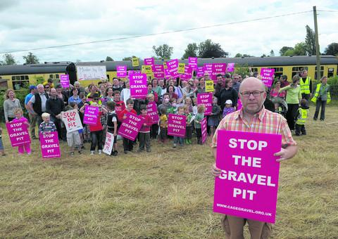 Mark Gray, front, and other campaigners beside the railway line