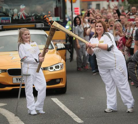 Two of the torch runners pass the flame in Bicester today