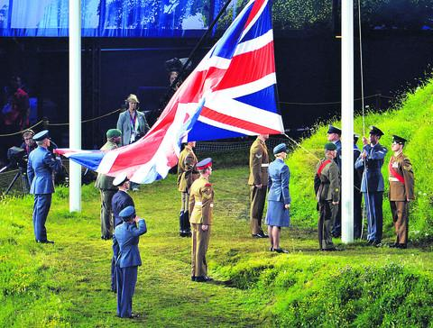 The Union Flag is carried into the stadium and raised by representatives of the Royal Navy, Army and Royal Air Force Royal Air Force personnel led by Squadron Leader Lambert from RAF Brize Norton