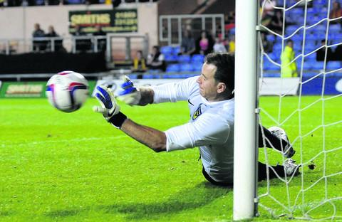 Oxford United goalkeeper Ryan Clarke dives to his left to save Marc Pugh's penalty and help his side to a 5-3 shoot-out victory over Bournemouth in the Capital One Cup at the Kassam Stadium