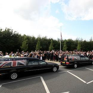 Friends and family lay flowers on the hearses of three servicemen killed in Afghanistan