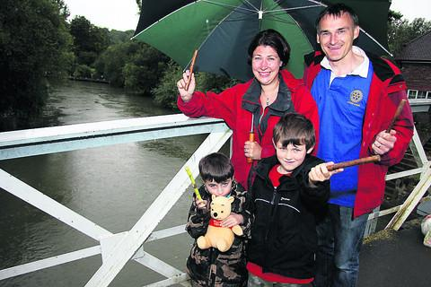 Event organiser Munro Watt with his wife Julie and children Douglas, five, and Cameron, seven, on the Pooh Sticks start point at the Thames.
