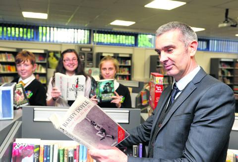 Carterton Community College Head Niall McWilliams with, left to right, Ashley White, 13, Amy Thomson, 14, and Eleanor Wheeler, 15, in the library