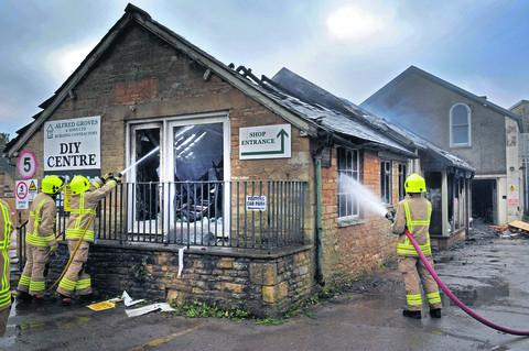 Firefighters damp down the building. Picture: Denis Kennedy