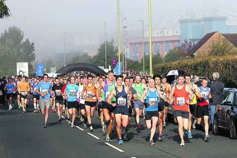 Competitors race away from the Oxford Half Marathon start line outside the mist-shrouded Kassam Stadium. Picture: OX54742 Ric Mellis