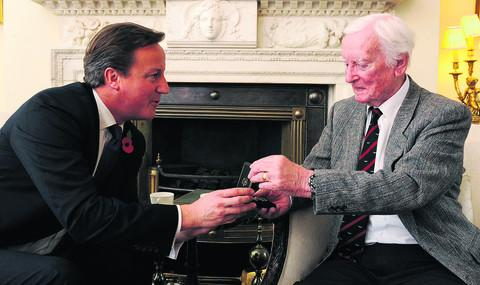 Prime Minister David Cameron presents Leslie Valentine with his medal