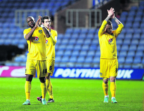 Justin Richards (left), Jake Wright and Sean Rigg (right) show their appreciation to the Oxford United fans after the 3-0 FA Cup defeat at home to Sheffield United on Saturday