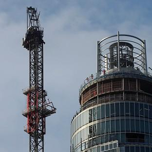 Construction workers view the damaged crane on top of St George's Tower