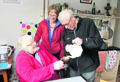 Ann Blake, left, gets a cup of tea from volunteer Eric Riley as scheme chairman Yvonne Milward looks on