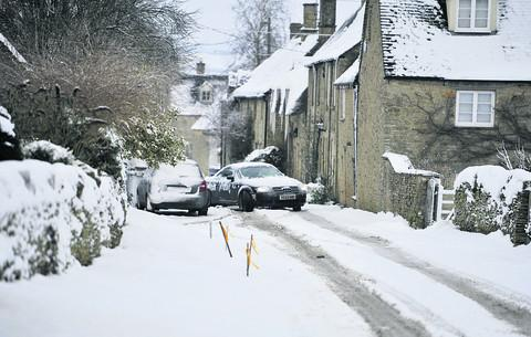 A car negotiates the street in Chilson, near Ascott-under-Wychwood where up to four inches of snow fell yesterday on top of five inches last week