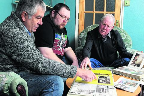 From left, Dave Powell, Andrew Blake and Bill Foley look through scrapbooks about Bruce Engineering.