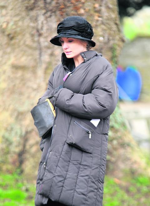 Joanne Froggatt stays warm during a break from filming