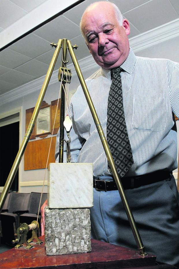 The Oxford Times: Former policeman and now Provincial Grand Charity Steward Roger Hampshire, from Bampton, pictured with a model of a traditional mason's hoist and two blocks of stone – intended to illustrate the Mason's spiritual journey from rough block to polished