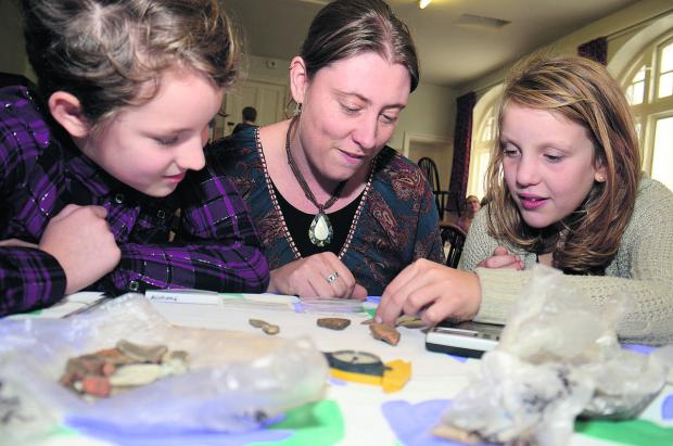 The Oxford Times: TREASURE: Anni Byard, centre, helps Lily Stevenson, 10, left, and Amy Godspeed, 10, identify their finds at Littlemore Village Hall