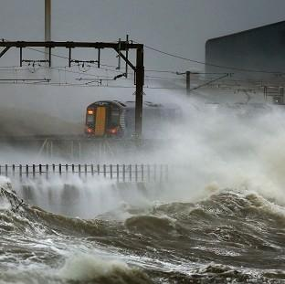 The Oxford Times: A train is lashed by waves along the coast at Saltcoats as Scotland has been warned to expect a storm surge.