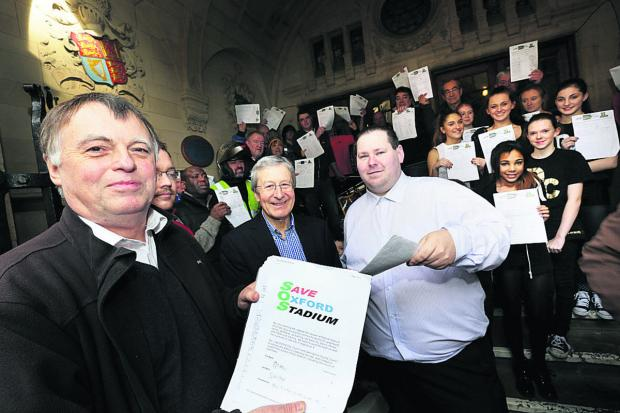 The Oxford Times: Oxford East MP Andrew Smith, left, and Save Oxford Stadium chairman Ian Sawyer, right, hand the SOS petition to city council leader, Bob Price, centre