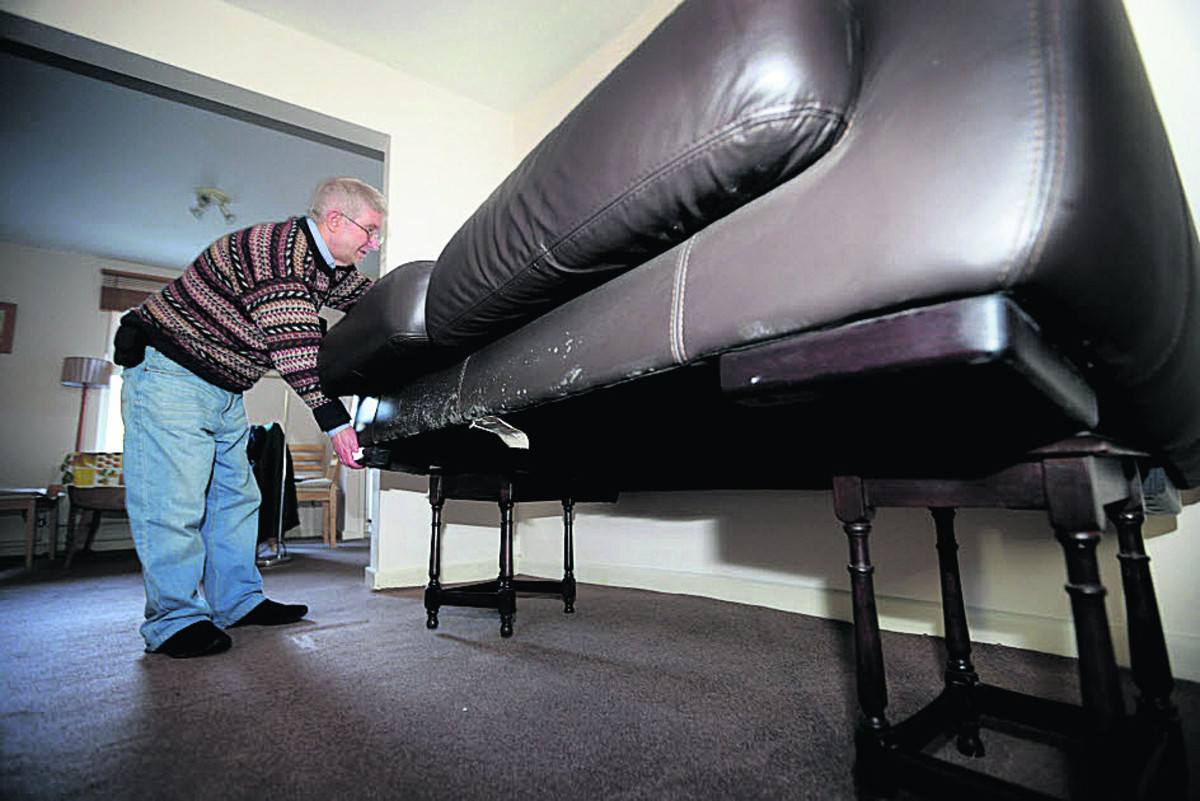 Andrew Ivett checks his sofa placed on tables as flood waters rise around his home in Earl Street