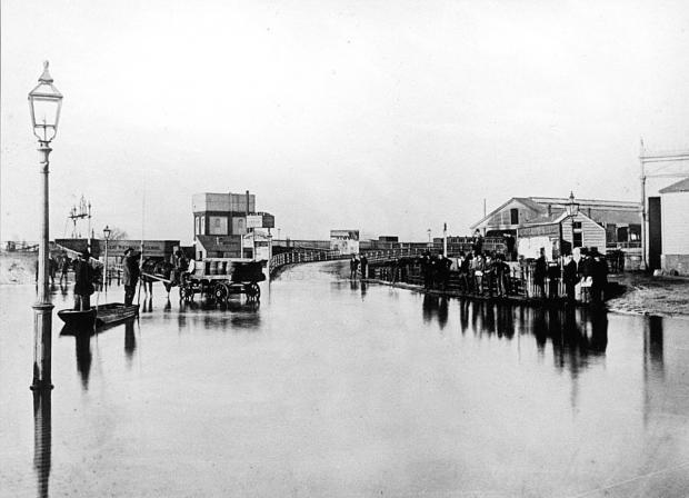 The Oxford Times: A punt was used during the floods of 1875 to ferry passengers to Oxford's Great Western Railway station, on the right, while the water under the railway bridge in Botley Road, on the left, was very deep