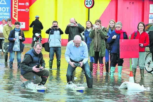John Brooks, left, in dark blue of Isis Creative Framing in Northampton Road, Oxford, decided to have a bit of fun in the floodwater on the Abingdon Road with a remote-control Varsity Boat Race Picture: OX64574 Jon Lewis