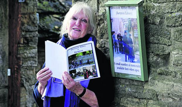 Jo Lewington reads one of the books containing photos of Downton filming taken by village locals