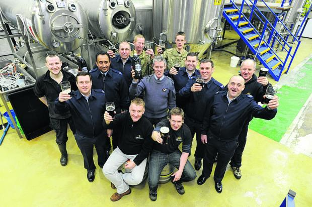 The Oxford Times: RAF Benson Reserves members raise a glass to new beer 606 with brewers Will Laithwaite and Chris Harrison (front from left).  Picture: OX64632 Jon Lewis