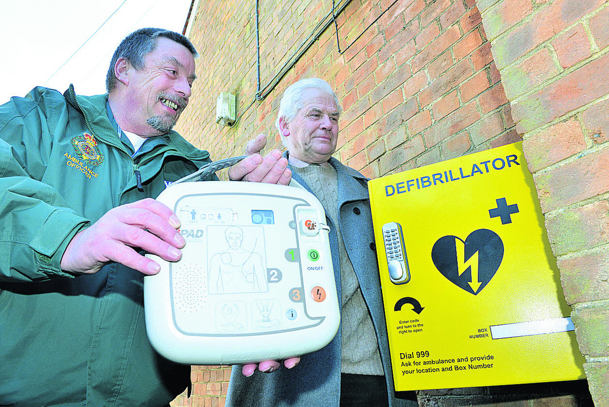 Dick Tracey of the Ambulance Service, left, with Michael Green, vice chairman of Combe Parish Council, with the new defibrillator at Combe village hall