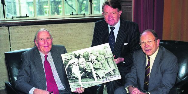 Chris Chataway, centre, and Chris Brasher holding up a photograph of Bannister breaking the four-minute mile in 1954. Chataway, the former 5,000 metres world record holder, acted as a pacemaker to help  Bannister become the first man to break the barrier