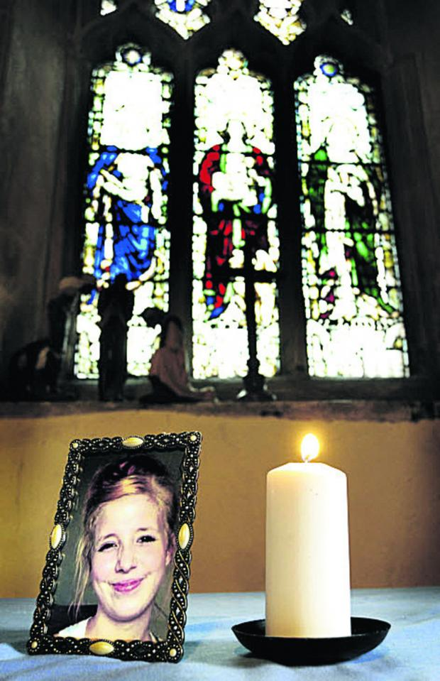 The Oxford Times: A candle burns next to a portrait of Jayden Parkinson at Didcot's All Saints Church