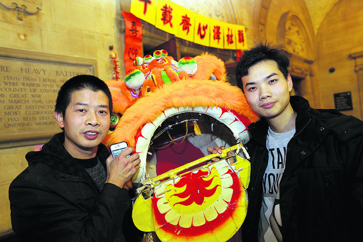 Zhang Tian Hu, left, and Ni Long pose with a lion as they marked the Chinese New Year
