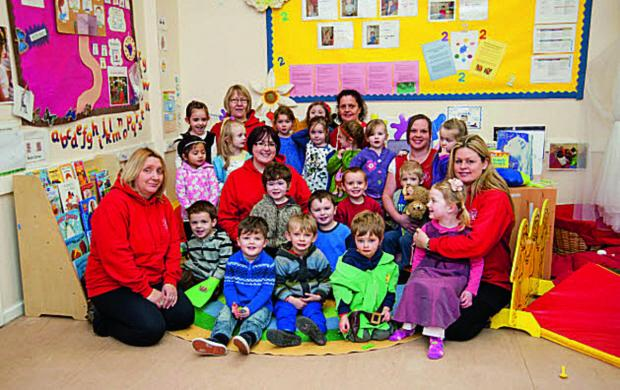 Rebecca Barker, centre in red, with staff and children at Jack and Jill