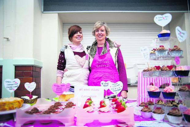 Emma Worthington, left, and Hilary Dollman of Sugar Rush selling some of their Valentine themed cupcakes at the weekly East Oxford community market. Picture: OX65047 Aimee Kirkham