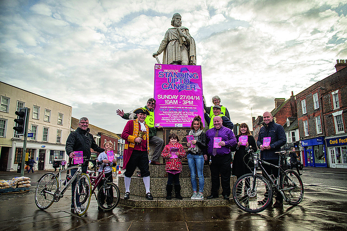 Wantage charity champion Ray Collins, third from right, with Maisie Norton, 15, and Mikayla Beames, seven, who have suffered cancer, joined by campaigners pushing the town's Standing Up to Cancer day