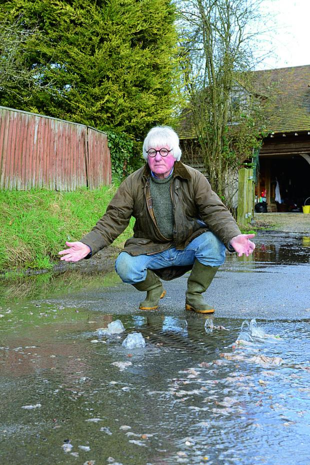 The Oxford Times: Frank Dumbleton shows sewage coming out of a manhole cover in The Lane, Chilton