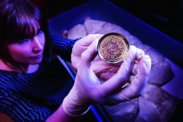 The Oxford Times: Project Officer Anna Griffiths with one of a pair of Ango-Saxon saucer brooches from 500-600 AD found at Watchfield. Picture: OX65095 Ed Nix