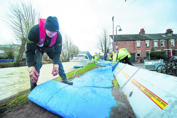 Dave Crook of the Environment Agency helps put up the flood defences in Osney Island, Oxford; right, scenes from the floods around the county