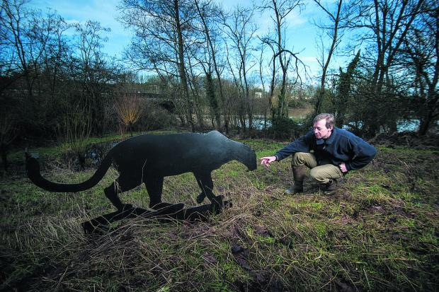 Philip Reid with the black panther statue in his garden Picture: OX65133 Andrew Walmsley