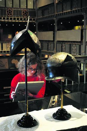 Artist Catherine Watson draws two helmets at the Pitt Rivers Museum