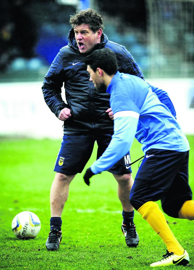 The Oxford Times: Mickey Lewis shouts the orders as he takes the pre-match warm-up at Bristol Rovers last week