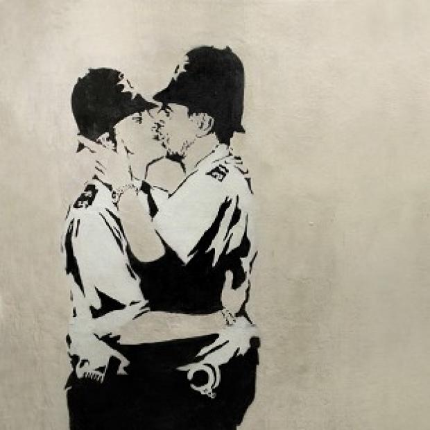"The Oxford Times: ""Kissing Coppers,"" a black-and-white stencil of two uniformed policeman in a passionate clinch by Banksy."