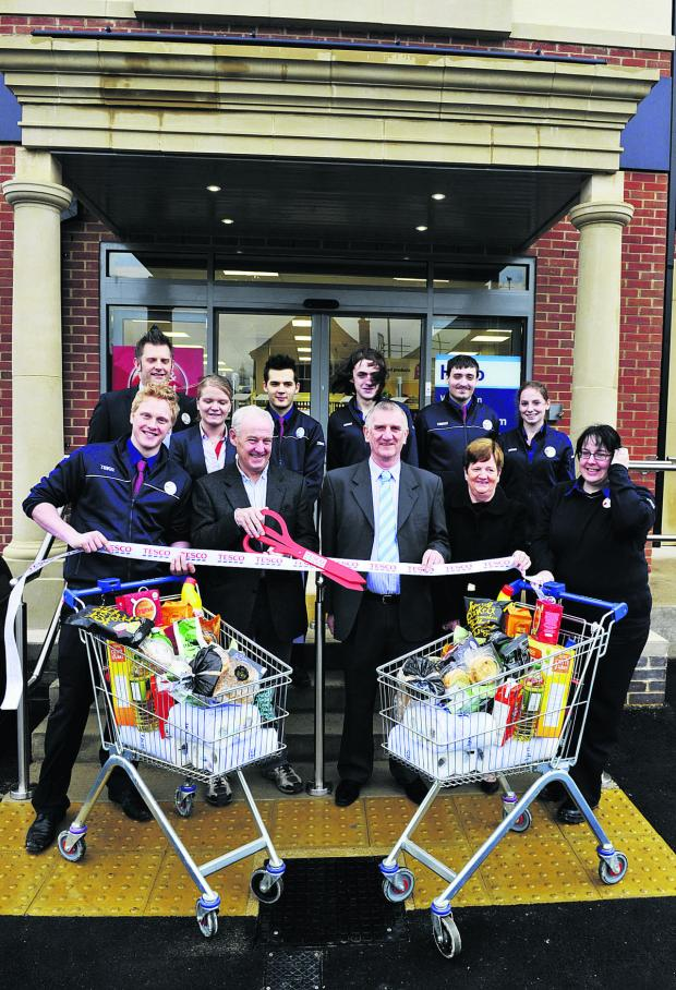 The Oxford Times: Tesco staff watch David Cairns, front, second from left, from Oxford Food Bank, William Rankin and Margaret Rankin open the new store