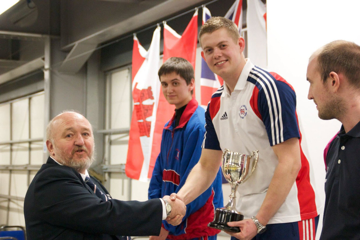 Didcot's Dan Rivers is presented with the British air rifle championship trophy by Roger Monksummers, as runner-up Jack Bale looks on