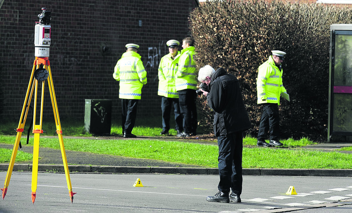 Police examine the scene of the accident Picture: David Fleming